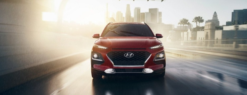 2021 Hyundai Kona red exterior front fascia driving on wet road outside of city
