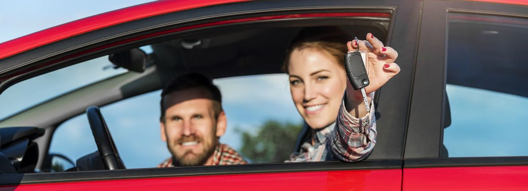 Couple in red car with woman holding key out window