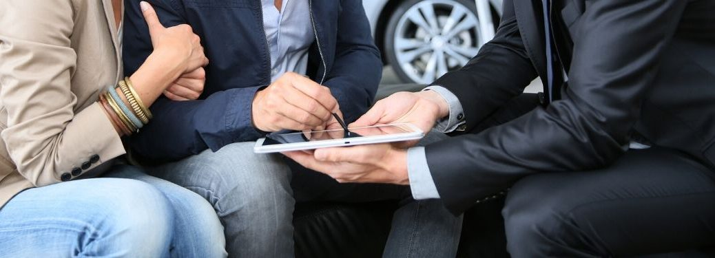 man signing ipad of salesman at car dealership