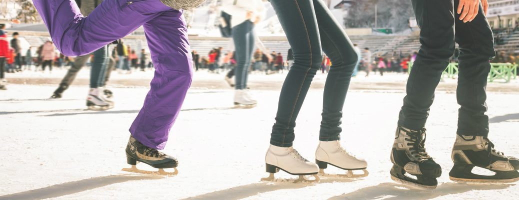 Three Friends Ice Skating Together at Rink