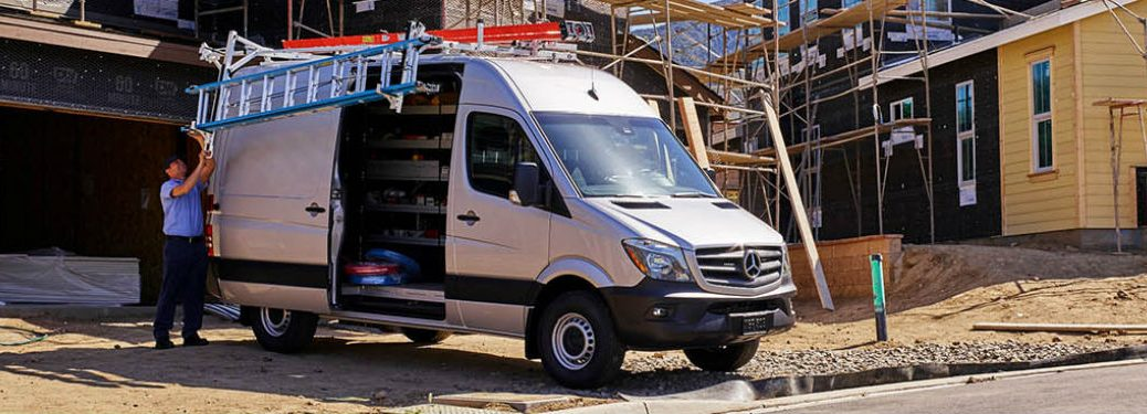 Passenger side exterior view of a 2019 Mercedes-Benz Sprinter Cargo Van parked at a job site with the side door open