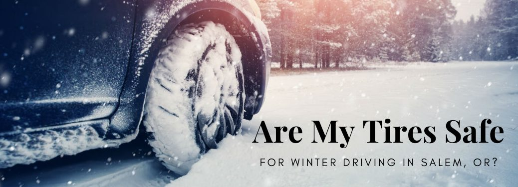 Are my tires safe for winter driving in Salem, OR?, text on an image of the front passenger side tire of a black car driving through a couple inches of snow