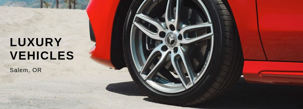 Luxury Vehicles Salem, OR, text on a closeup image of the front driver side tire and rim of a red 2019 Mercedes-Benz CLA Coupe