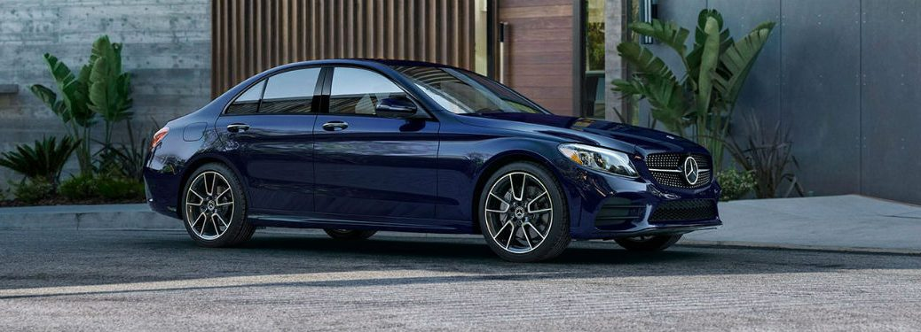 2020 MB C Class sedan blue exterior passenger side slight front fascia in front of building