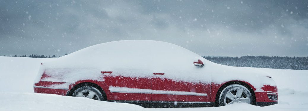 red car in snow pile and covered in snow