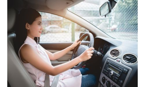 woman driving car wearing pink blouse and jeans