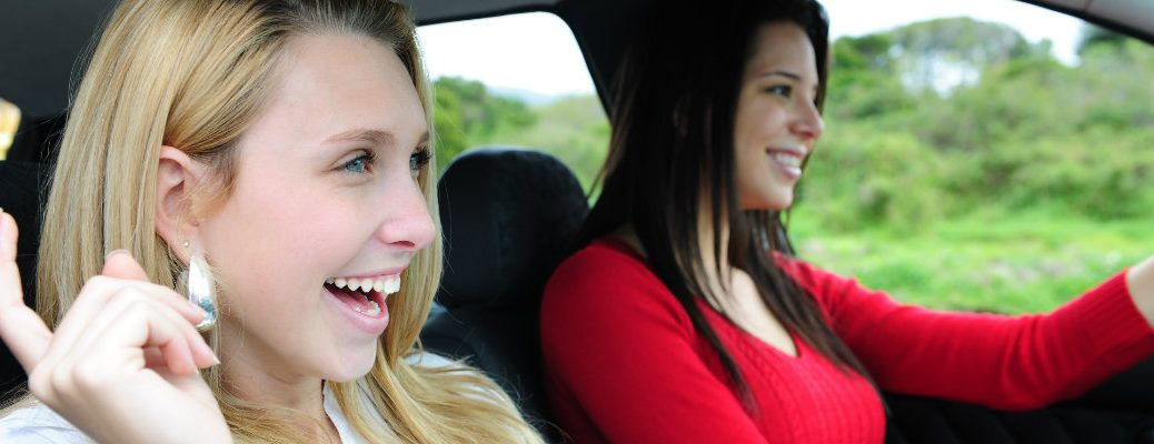 2 women listening to a podcast in a car