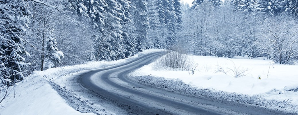 Curved road covered in ice and snow with a wooded area on both sides