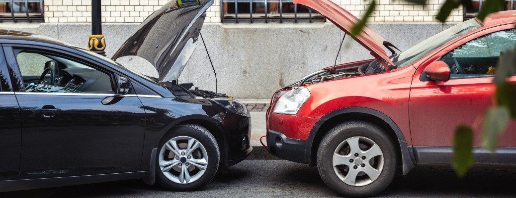 A blue car and a red car using jumper cables to jump-start the other