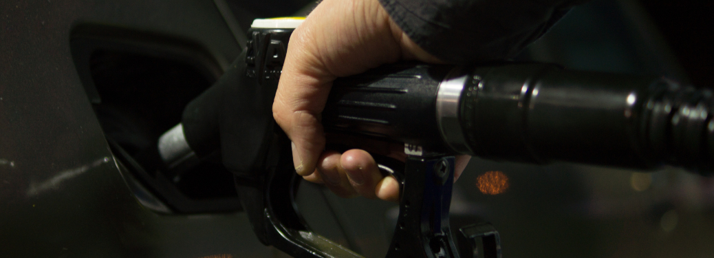 Close up on a person's hand using a gas pump to refuel a vehicle