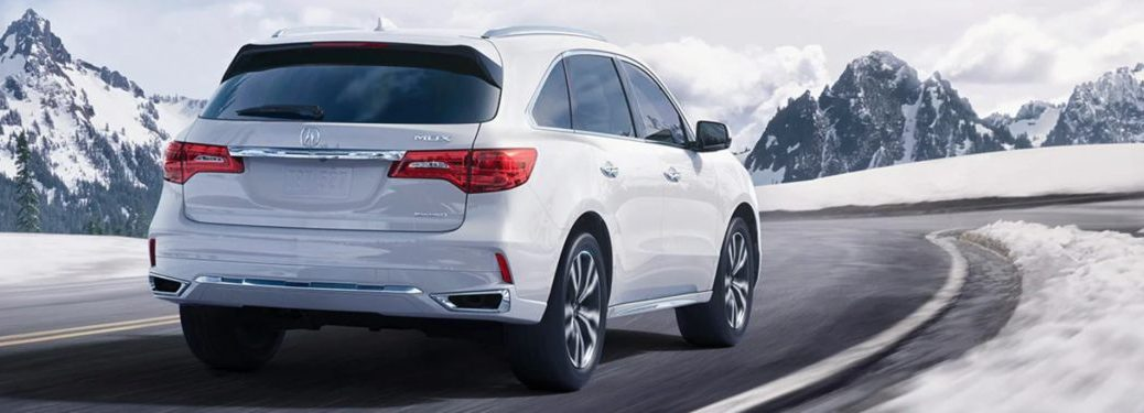 2020 Acura MDX driving down a snowy, winding road