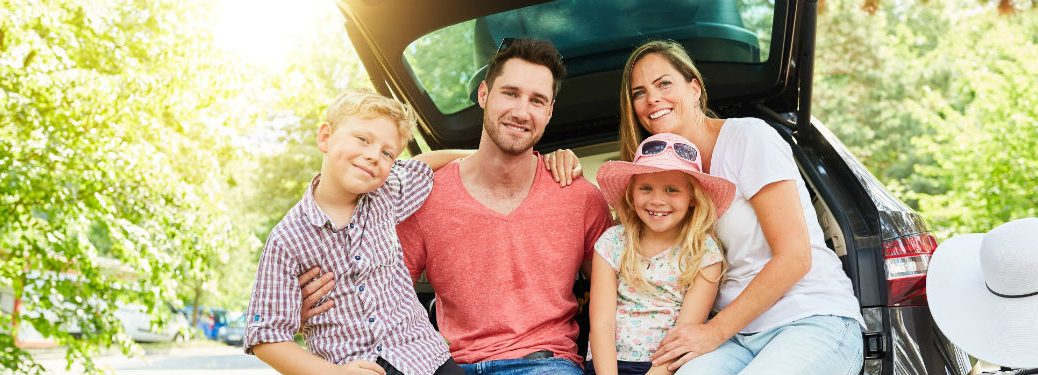 happy family of four sitting on back end of vehicle