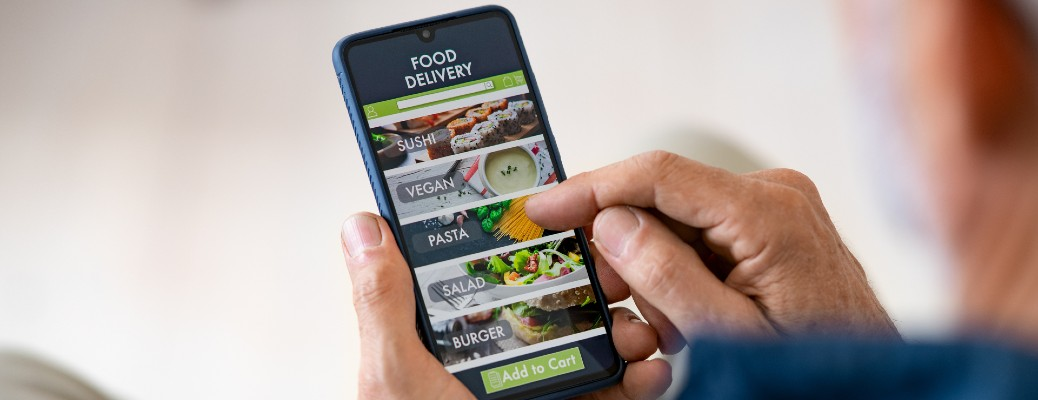 man holding phone and using food delivery app