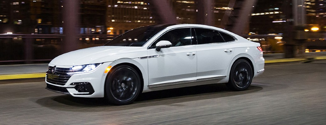 2020 VW Arteon white exterior front driver side driving on bridge in city at night