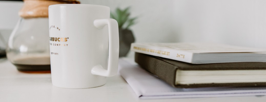 white coffee mug next to small stack of books