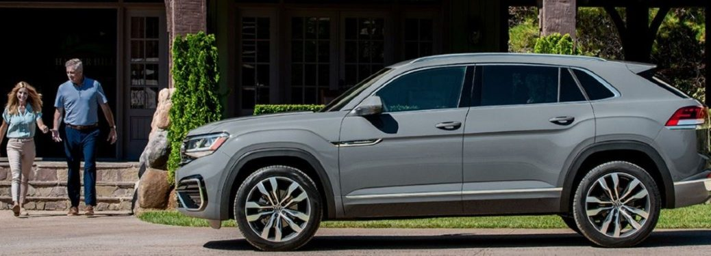 2020 VW Atlas Cross Sport grey exterior driver side parked on street couple walking out of building