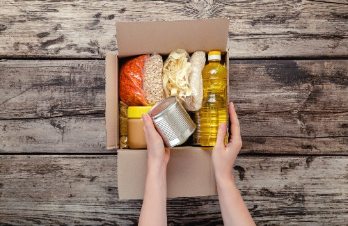 person packing box of food donations