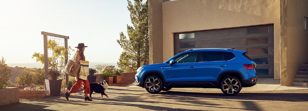 2022 VW Taos blue exterior driver side parked in driveway woman and her dog walking toward Taos