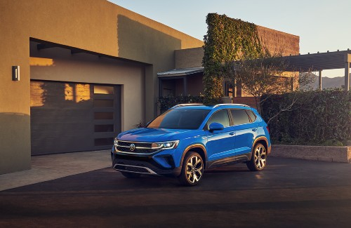 2022 VW Taos blue exterior front fascia driver side facing parked in driveway of house in mountains