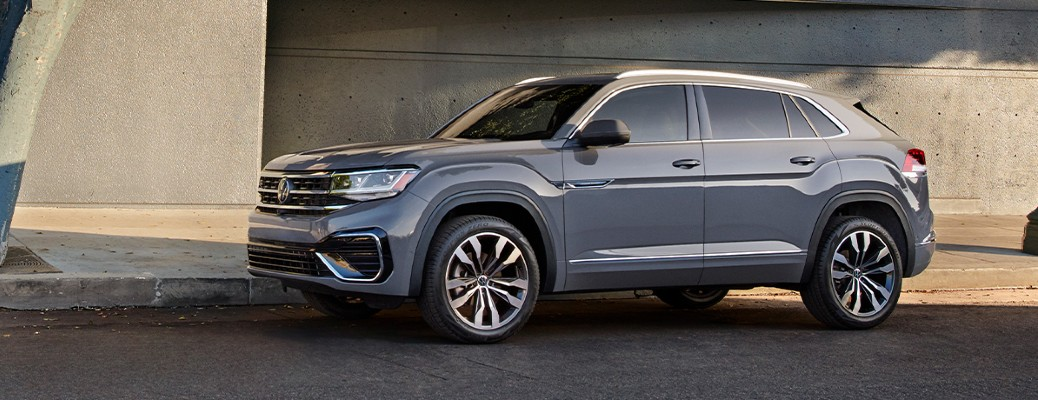 The side view of a gray 2021 Volkswagen Atlas Cross Sport parked on the side of a street.