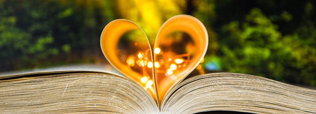 book open with two pages forming heart with fairy lights