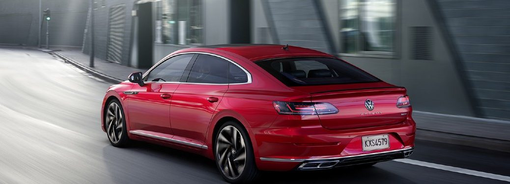 2021 VW Arteon red exterior rear driver fascia driving on curvy road in city