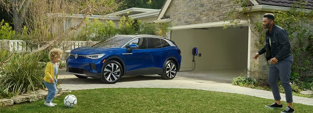 2021 VW ID.4 blue exterior parked and charging in driveway father playing soccer with child