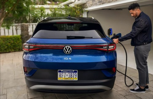 2021 VW ID.4 blue exterior rear fascia parked in driveway man plugging in charging cable