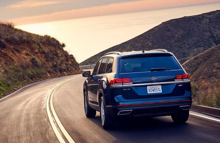 Rear view of a 2022 VW Atlas driving through the mountainside.