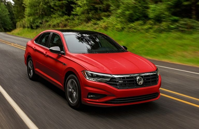Front view of a red 2021 VW Jetta driving on a highway.