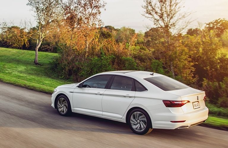 White 2021 VW Jetta driving through a country road.