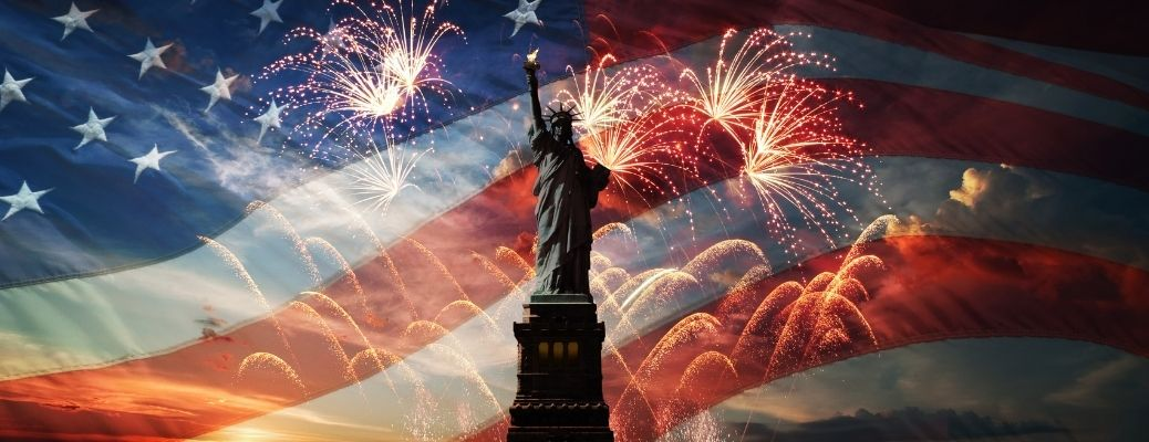 Statue of Liberty with the American Flag and fireworks in background.