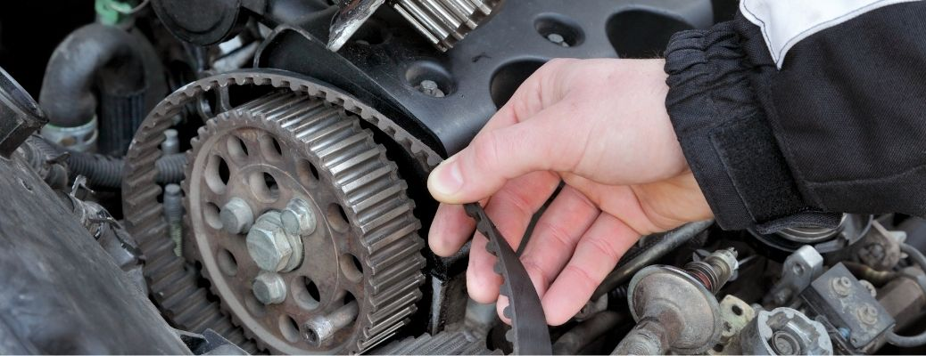 Hand removing the timing belt from a Volkswagen vehicle