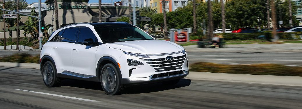 white Hyundai NEXO driving down city street