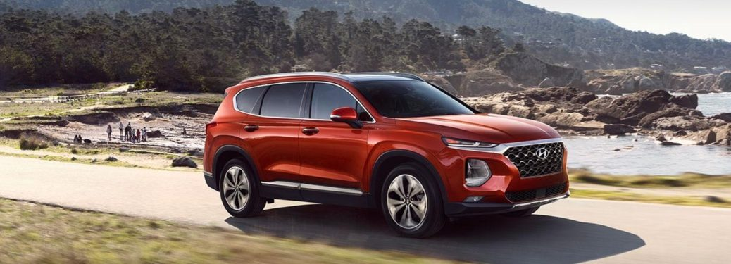 Red 2019 Hyundai Santa Fe driving along trail