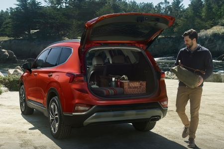 Man walking beside 2019 Hyundai Santa Fe with the trunk open