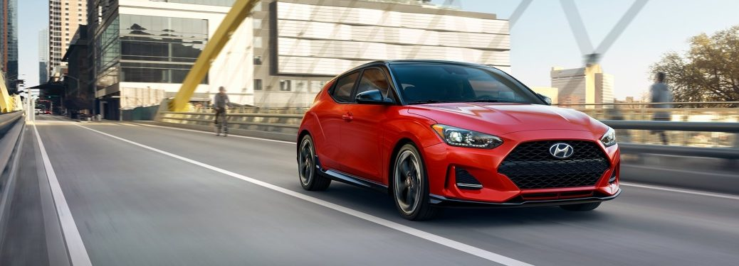 Red 2020 Hyundai Veloster driving across bridge