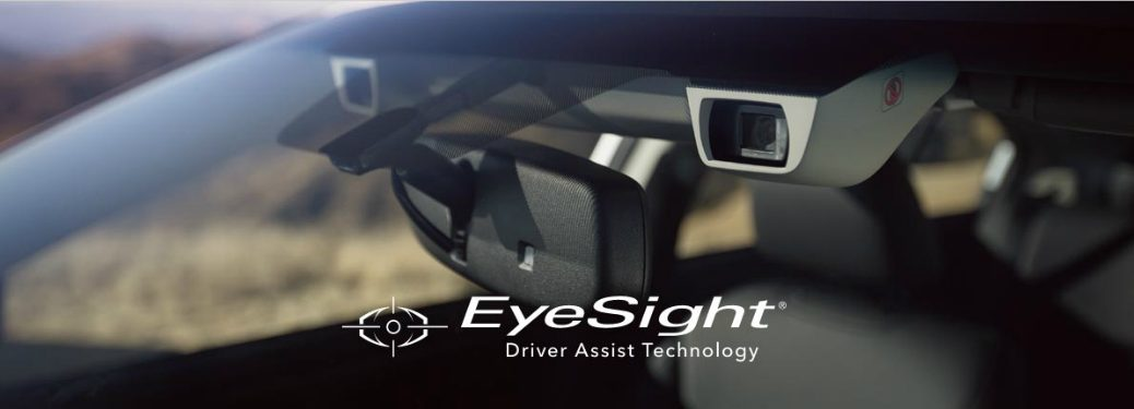 "view of rearview mirror and cameras through windshield with overlaid text that says ""EyeSight Driver Assist Technology"""