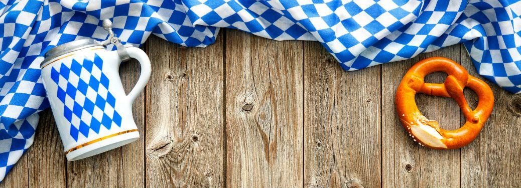 oktoberfest themed table cloth on a wood table with stein and pretzel