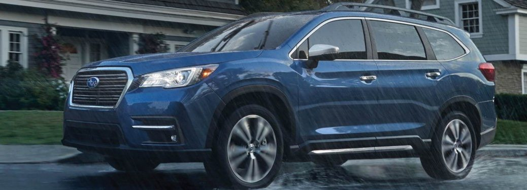 2019 Subaru Ascent driving through a suburban street in the rain