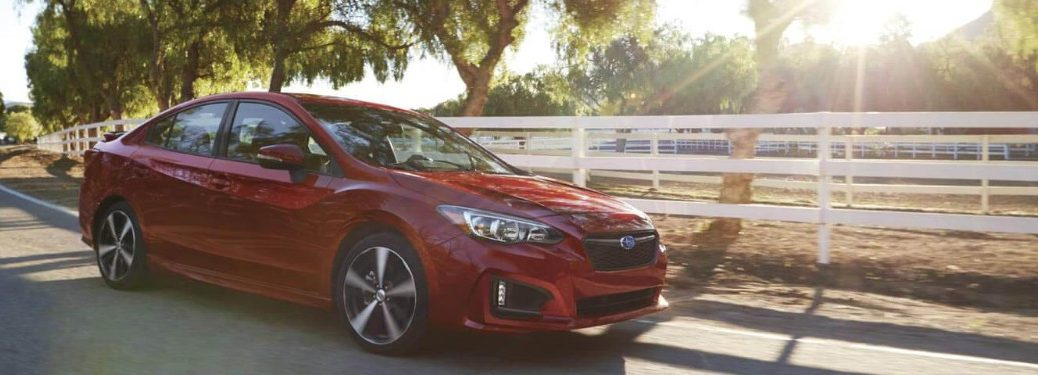 Red 2019 Subaru Impreza Driving Down the Road on a Sunny Day