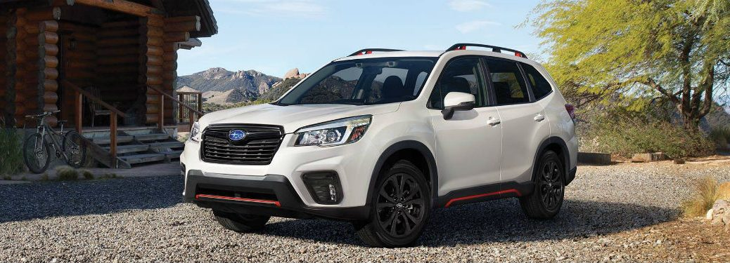 2019 Subaru Forester exterior front fascia and driver side in front of log cabin with tree