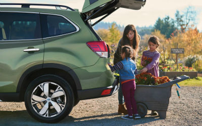 2019 Subaru Forester exterior back half of driver side with mother and 2 children loading vehicle