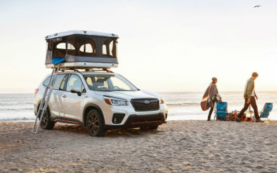 2019 Subaru Forester exterior front fascia and passenger side on beach with man couple to right