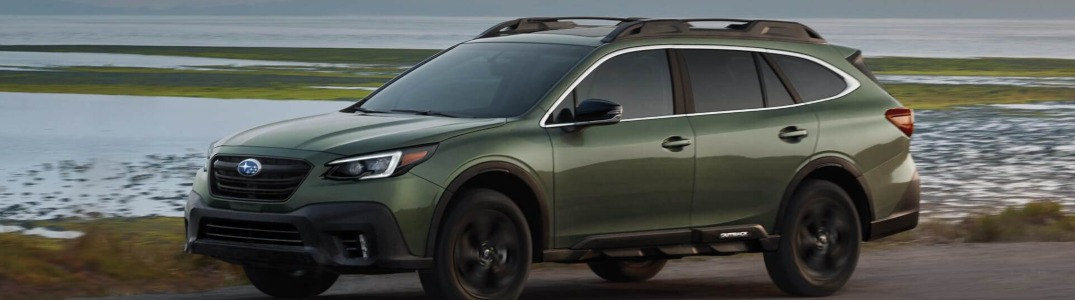 2020 Subaru Outback driving by a lake