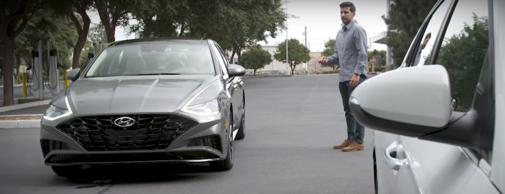 A man using the Remote Park Assist feature with a grey Hyundai Sonata