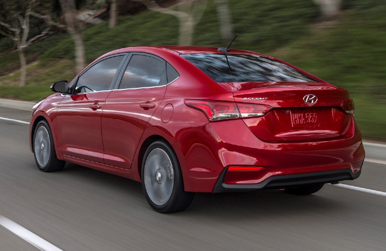 Driver's side rear angle view of red 2021 Hyundai Accent