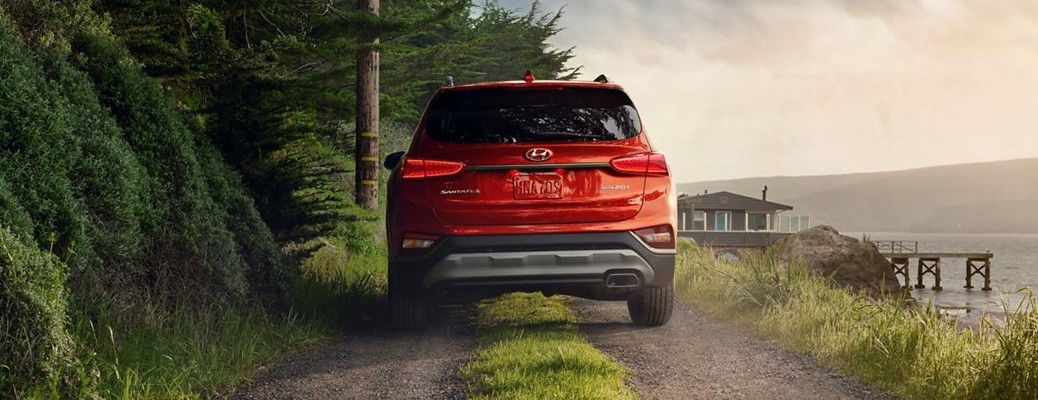 Red 2020 Hyundai Santa Fe driving on a coastal road