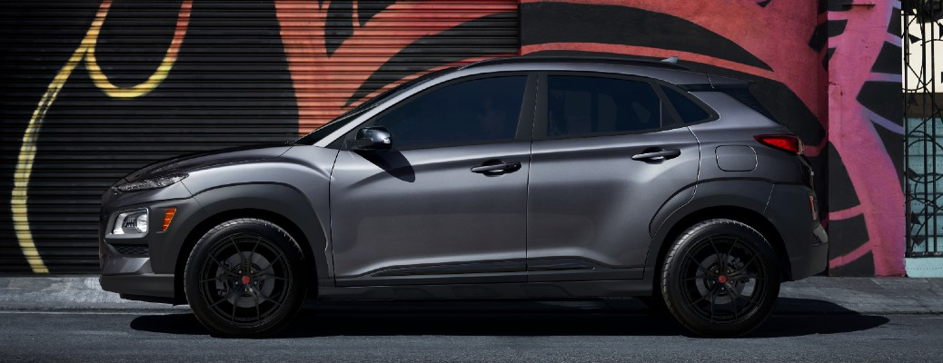 Dark gray and black 2021 Hyundai Kona Night Edition parked in front of a colorful wall