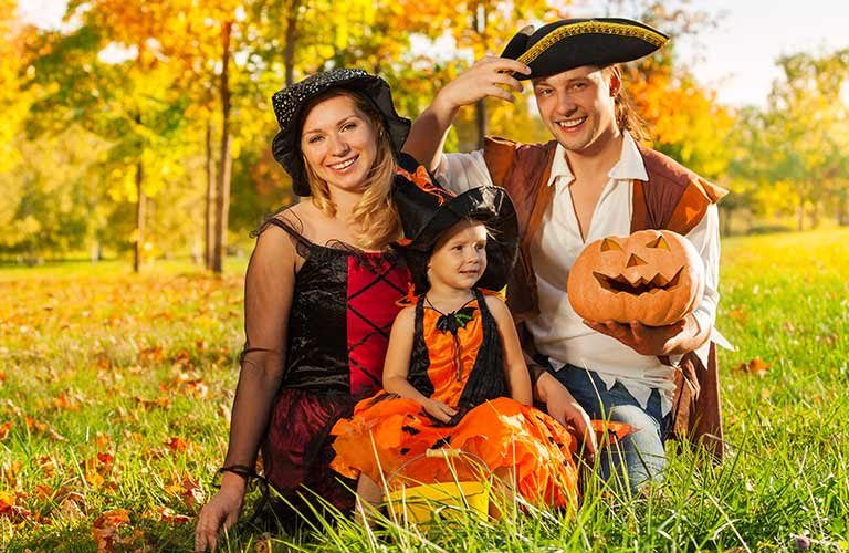 Family in Costumes with Pumpkins in a Yard